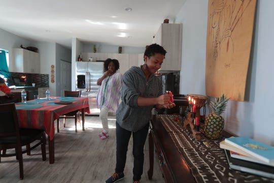 Gye Nyame Maat lights candles to place on to the kinara to celebrate Kwanzaa, on Saturday, December 29, 2018 in Desert Hot Springs. The weeklong pan-African holiday  celebrates family, community and culture. Each of the seven candles represents on of the seven principles of Kwanzaa
