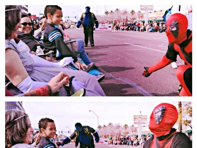 Deadpool bows and kisses the hand of Karen Bayless Feldman along the Fiesta Bowl Parade route in 2013.