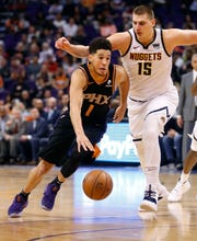 Phoenix Suns guard Devin Booker (1) drives as Denver Nuggets center Nikola Jokic (15) defends during the second half of an NBA basketball game, Saturday, Dec. 29, 2018, in Phoenix.