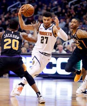 Denver Nuggets guard Jamal Murray (27) drives against Phoenix Suns forward Josh Jackson (20) during the first half of an NBA basketball game, Saturday, Dec. 29, 2018, in Phoenix.
