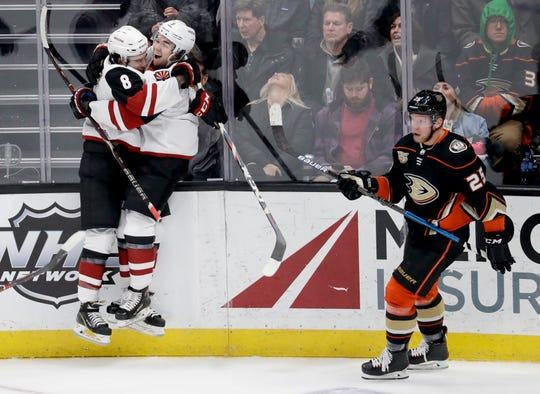 Arizona Coyotes center Nick Schmaltz, left, celebrates with Clayton Keller after scoring in overtime, as Anaheim Ducks right wing Ondrej Kase skates past in an NHL hockey game in Anaheim, Calif., Saturday, Dec. 29, 2018.