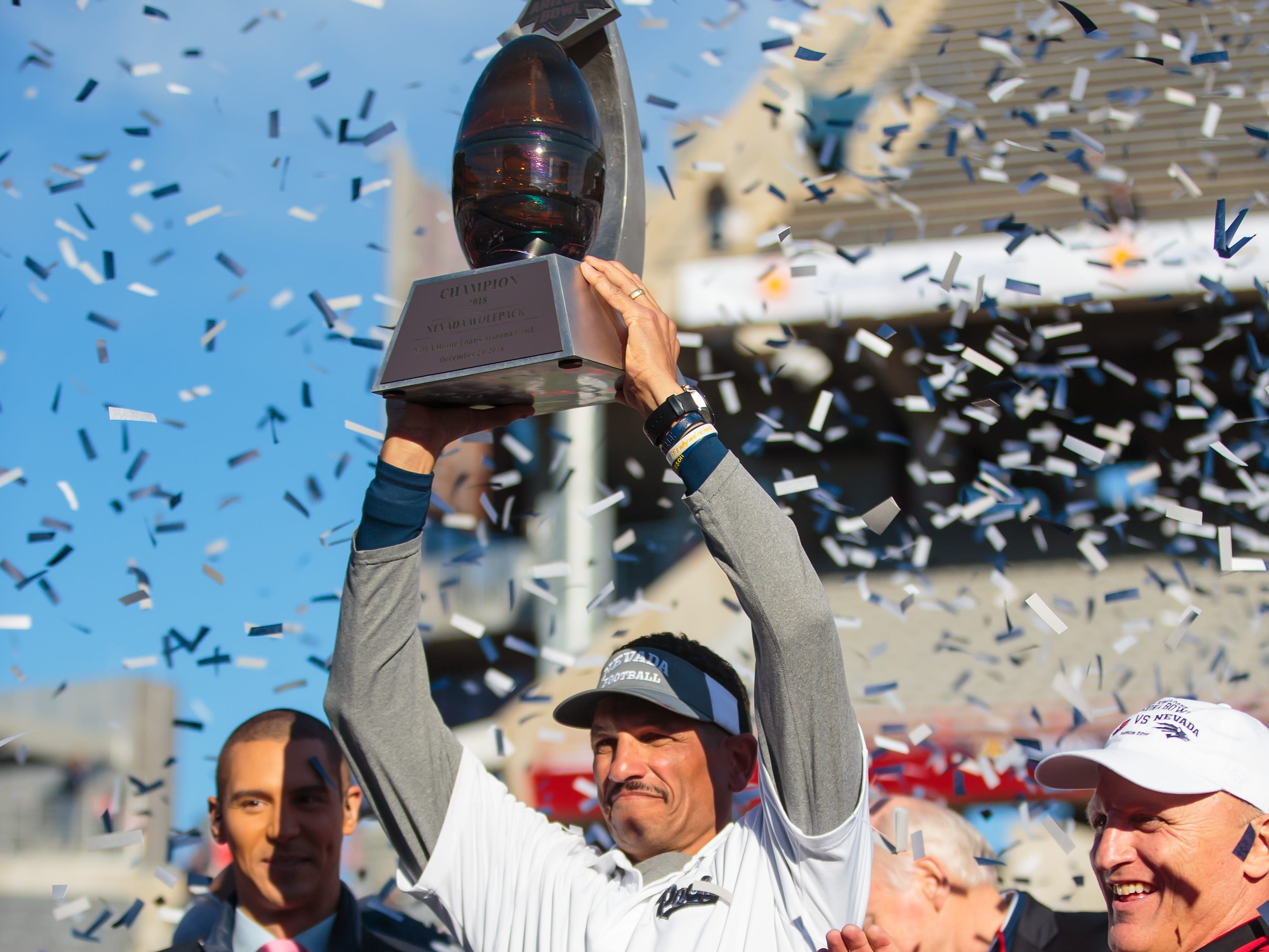 Dec 29, 2018; Tucson, AZ, USA; Nevada Wolf Pack head coach Jay Norvell celebrates with the trophy after defeating the Arkansas State Red Wolves in overtime of the 2018 Arizona Bowl at Arizona Stadium.
