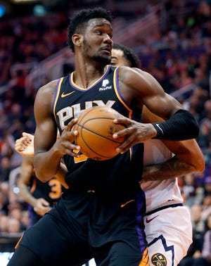 Phoenix Suns center Deandre Ayton (22) backs against the Denver Nuggets during the second half of an NBA basketball game, Saturday, Dec. 29, 2018, in Phoenix.