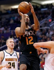 Phoenix Suns' T.J. Warren (12) shoots as Denver Nuggets forward Mason Plumlee (24) looks on during the second half of an NBA basketball game, Saturday, Dec. 29, 2018, in Phoenix.
