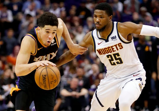 Phoenix Suns guard Devin Booker (1) drives as Denver Nuggets guard Malik Beasley (25) defends during the second half of an NBA basketball game, Saturday, Dec. 29, 2018, in Phoenix.