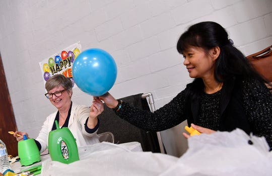 Volunteers Judy Vance, left, and Angie Shirey inflate some of the nearly 3,000 balloons while setting up for the New Year's Eve Children's Countdown in Voni Grimes Gym, Sunday, December 30, 2018.John A. Pavoncello photo