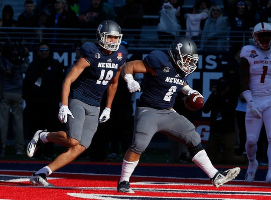 Nevada running back Devonte Lee (2) celebrates with Cole Turner after scoring with 1:06 left in the game Saturday. It was the Wolf Pack's only touchdown in regulation.