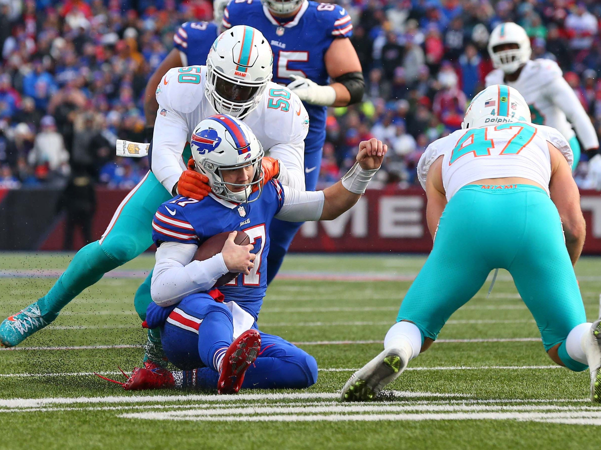 Dec 30, 2018; Orchard Park, NY, USA; Buffalo Bills quarterback Josh Allen (17) slides after a run as Miami Dolphins defensive end Andre Branch (50) and outside linebacker Kiko Alonso (47) defend during the third quarter at New Era Field. Mandatory Credit: Rich Barnes-USA TODAY Sports