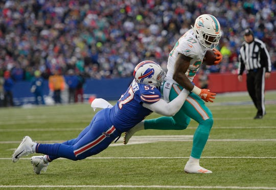 Buffalo Bills outside linebacker Lorenzo Alexander (57) tackles Miami Dolphins running back Kalen Ballage (27) after a one-yard catch during the second half of an NFL football game, Sunday, Dec. 30, 2018, in Orchard Park, N.Y. (AP Photo/Adrian Kraus)