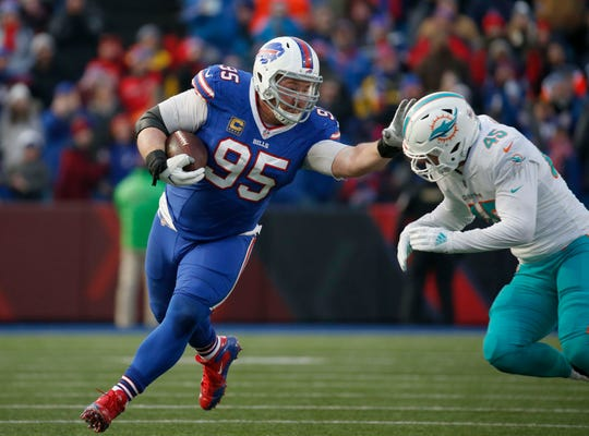 Dec 30, 2018; Orchard Park, NY, USA; Buffalo Bills defensive tackle Kyle Williams (95) runs the ball after a catch while Miami Dolphins linebacker Mike Hull (45) looks to make a tackle during the second half at New Era Field. Mandatory Credit: Timothy T. Ludwig-USA TODAY Sports