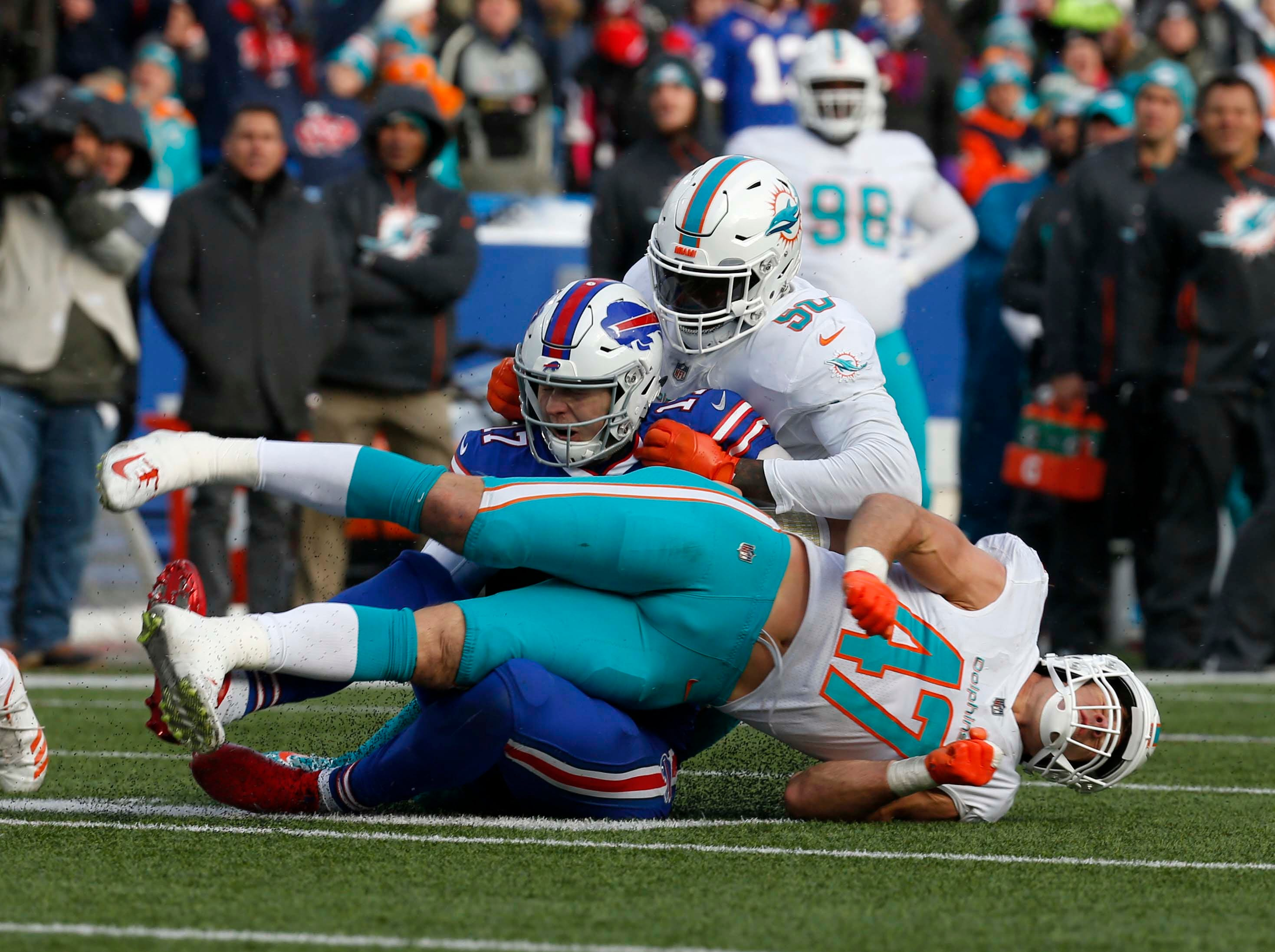 Dec 30, 2018; Orchard Park, NY, USA; Miami Dolphins defensive end Andre Branch (50) tries to tackle Buffalo Bills quarterback Josh Allen (17) as he runs the ball and slides while taking a late hit from Miami Dolphins outside linebacker Kiko Alonso (47) during the second half at New Era Field. Mandatory Credit: Timothy T. Ludwig-USA TODAY Sports