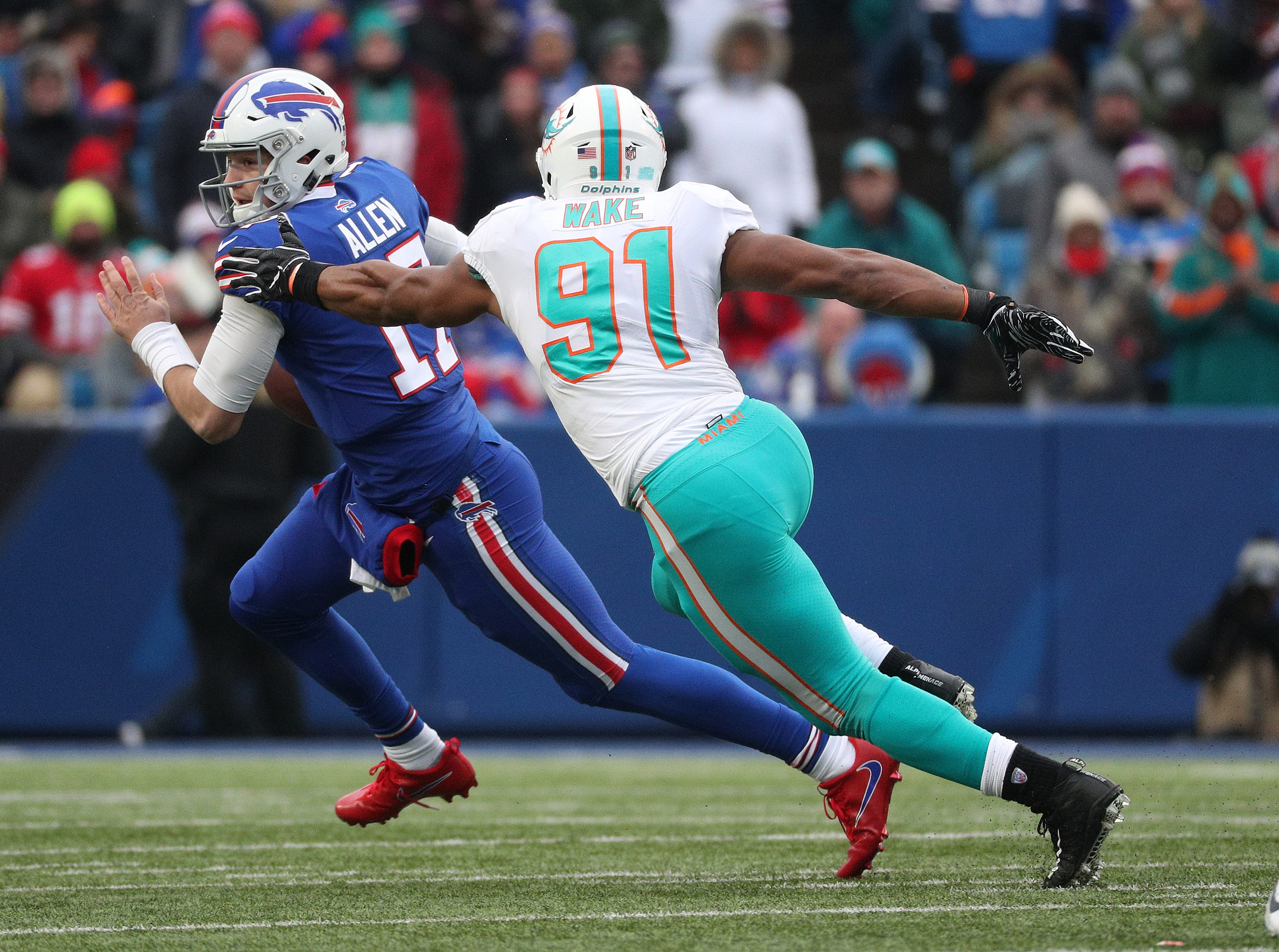 Bills quarterback Josh Allen rolls away from Dolphins Cameron Wake.