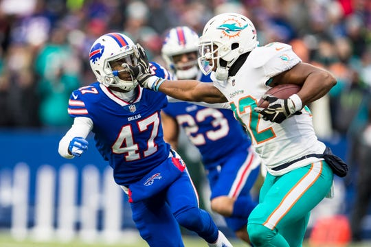 Kenyan Drake of the Miami Dolphins stiff arms Levi Wallace of the Buffalo Bills during the first quarter of the Dec. 30 season finale at New Era Field.