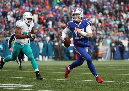 Bills quarterback Josh Allen looks downfield as he scrambles away from pressure.