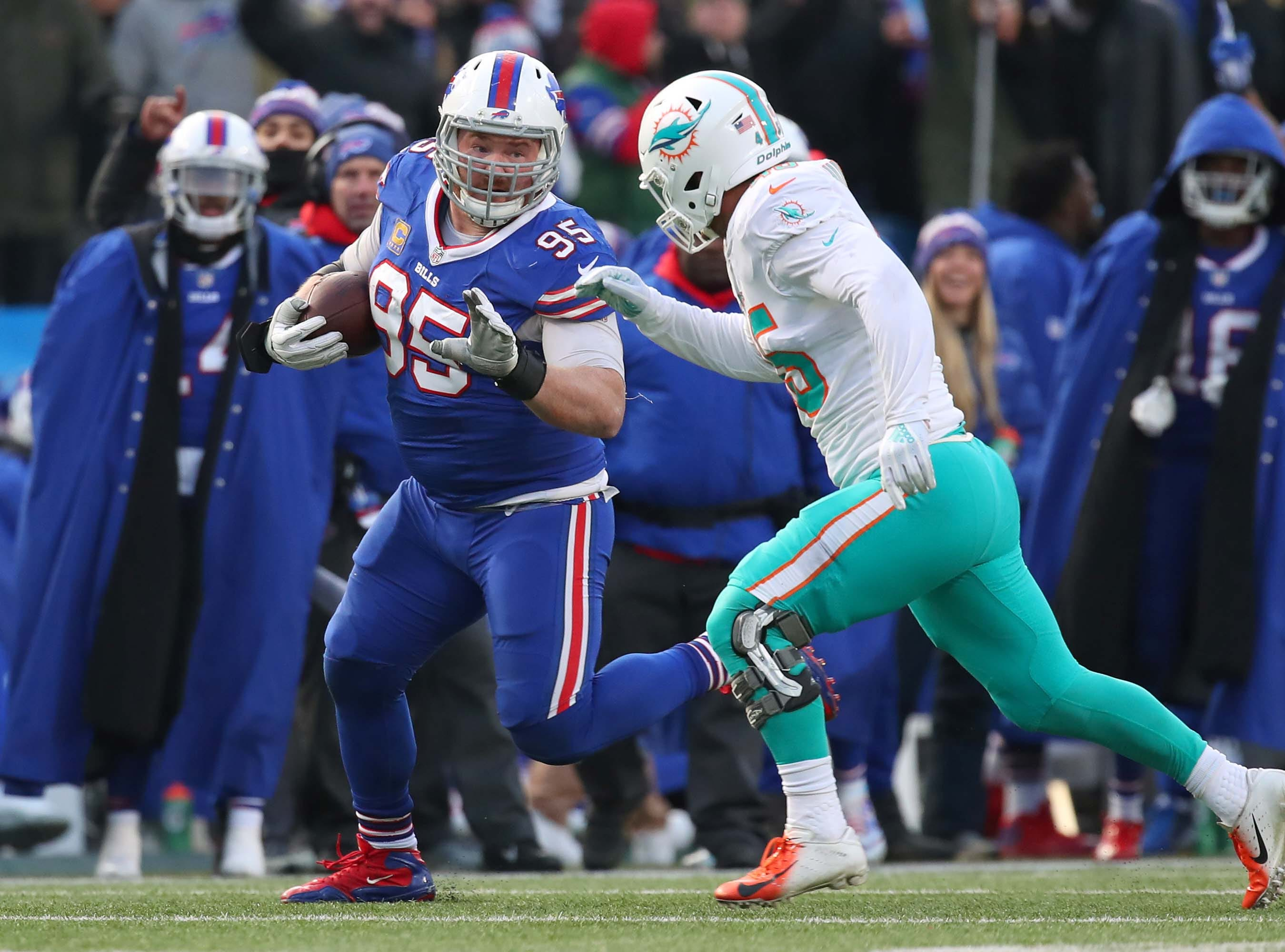 Dec 30, 2018; Orchard Park, NY, USA; Buffalo Bills defensive tackle Kyle Williams (95) runs with the ball after a catch as Miami Dolphins linebacker Mike Hull (45) defends during the fourth quarter at New Era Field. Mandatory Credit: Rich Barnes-USA TODAY Sports