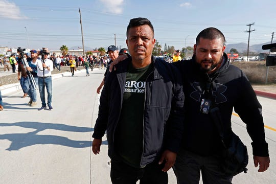"""Irineo Mujica, activist with """"Pueblo Sin Fronteras,"""" or People Without Borders, center, is accompanied by an unidentified man as he enters the U.S. consulate Dec. 11, during a demonstration by Central American migrants in Tijuana, Mexico.  The activist group that escorted thousands of Central Americans to the U.S. border is under fire from allies and some of the migrants themselves. They say the organization downplayed the dangers of the trek and misled them about how long they would have to wait around to apply for asylum. Pueblo Sin Fronteras, or People Without Borders, is defending itself, saying the migrants made their own decision to press on toward the United States. (AP Photo/Moises Castillo)"""