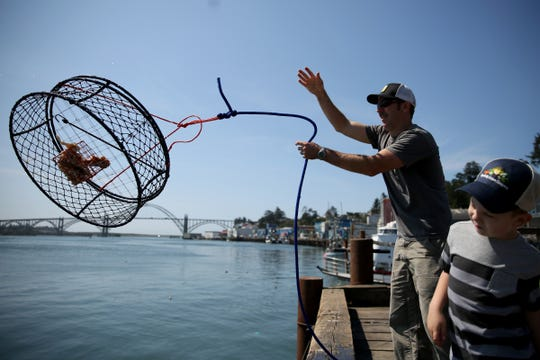 Mike Dill, 36, of Philomath, tosses a crabbing cage into the Yaquina Bay as his son Noah Dill, 5, watches in Newport on Aug. 19.