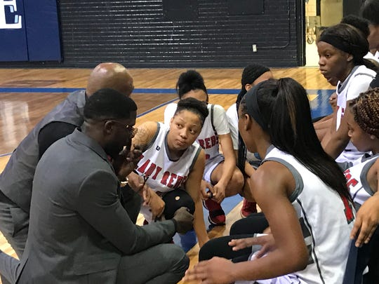 """North Caddo coaches Brian Shyne and Rickey Evans discuss strategy with their team during the 2018 """"Doc"""" Edwards championship game Saturday night."""