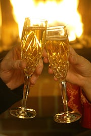 Toast with Champagne at home on New Year's Eve in front of a roaring fire.