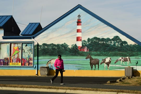 A pedestrian walks past a mural depicting the wild ponies of Chincoteague.