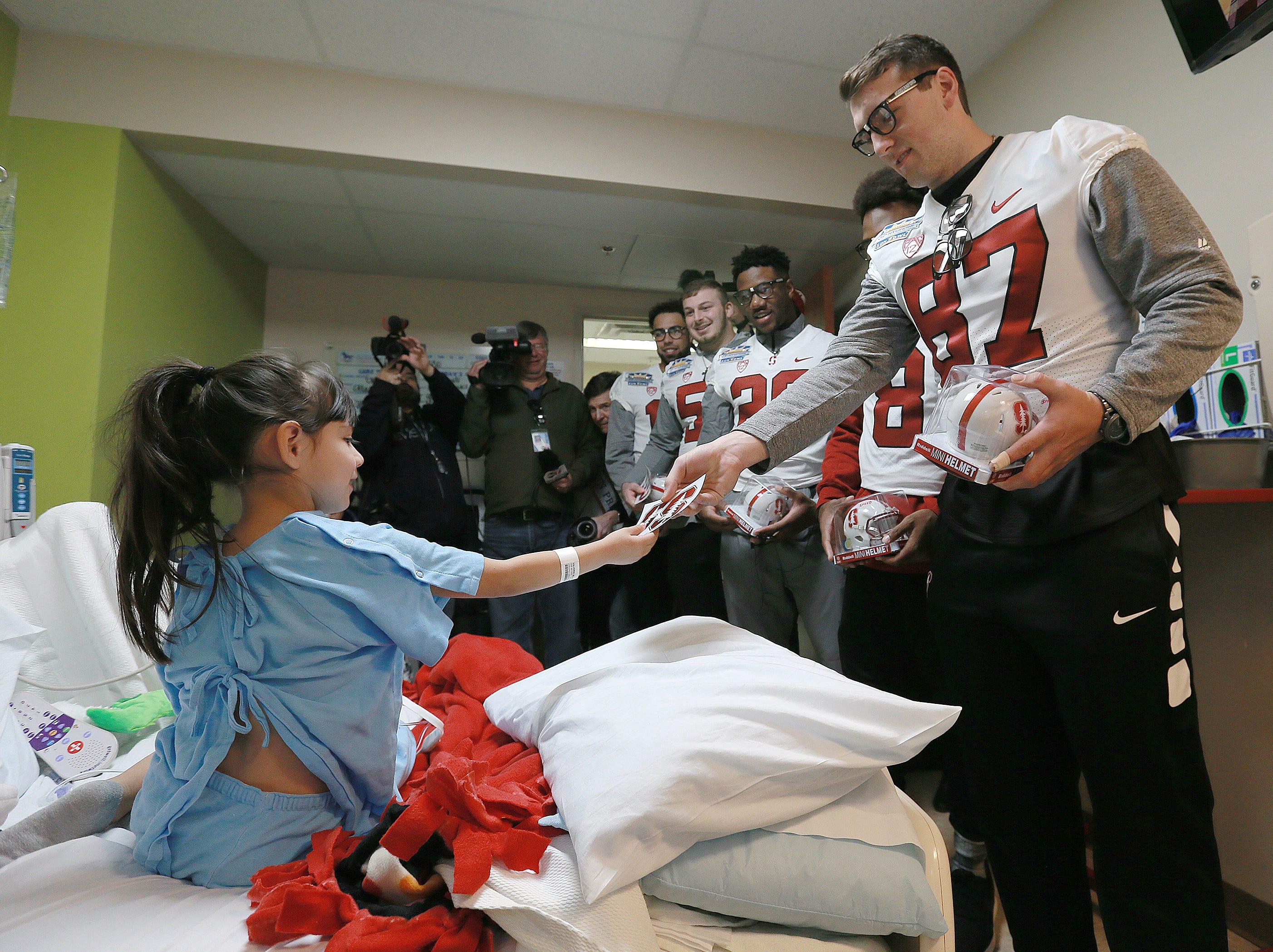 Stanford senior fullback Ben Snyder hands Stanford stickers to Providence Children's Hospital patient Bella Valverde during the team's visit Sunday.