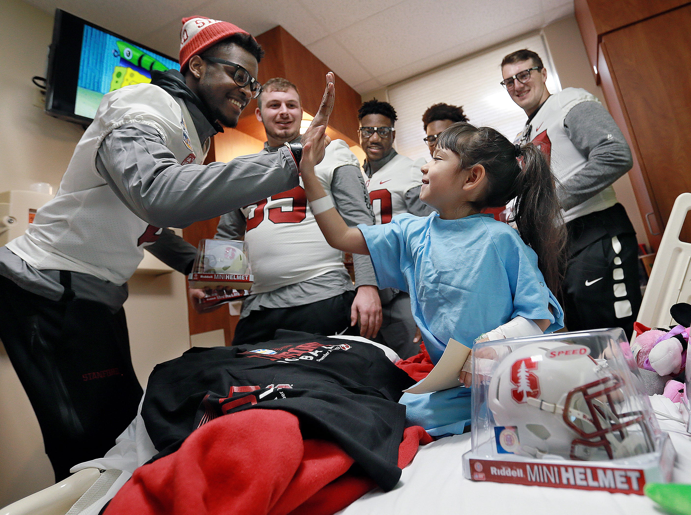 Bella Valverde, 5, gives Stanford junior wide receiver Donald Stewart a high five during the team's visit to Providence Children's Hospital Sunday as Pitt players visit kids at El Paso Children's Hospital. The teams face off New Year's Eve at noon in the Hyundai Sun Bowl.