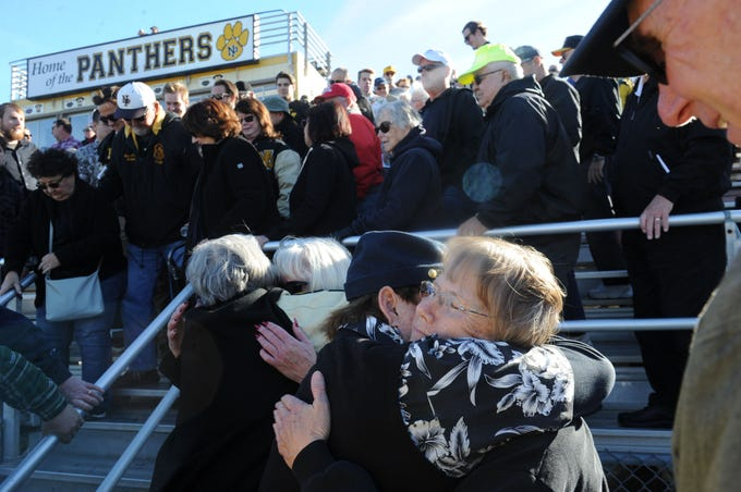 Berta Hurley, right, receives hugs of support after a tribute for her husband, George Hurley, who died on Nov. 19, at the Newbury Park High school football stadium Saturday.