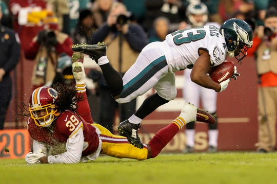 Philadelphia Eagles running back Darren Sproles (43) is kicked off his feet by Washington Redskins defensive back Adonis Alexander (39) during the first half of the NFL football game, Sunday, Dec. 30, 2018 in Landover, Md. (AP Photo/Andrew Harnik)
