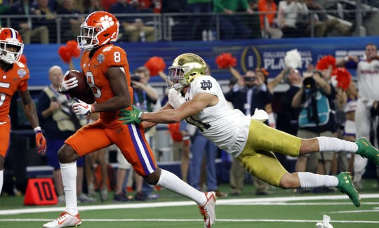 Clemson wide receiver Justyn Ross (8) escapes a tackle attempt by Notre Dame safety Alohi Gilman, right, as Ross reaches the end zone for a touchdown in the first half of the NCAA Cotton Bowl semi-final playoff football game, Saturday, Dec. 29, 2018, in Arlington, Texas.