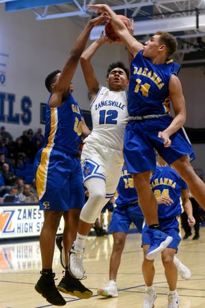 Zanesville's Cory Norris is met by a pair of defenders in the lane during the third quarter of Zanesville's 55-42 loss to visiting Gahanna on Saturday night at Winland Memorial Gymnasium.