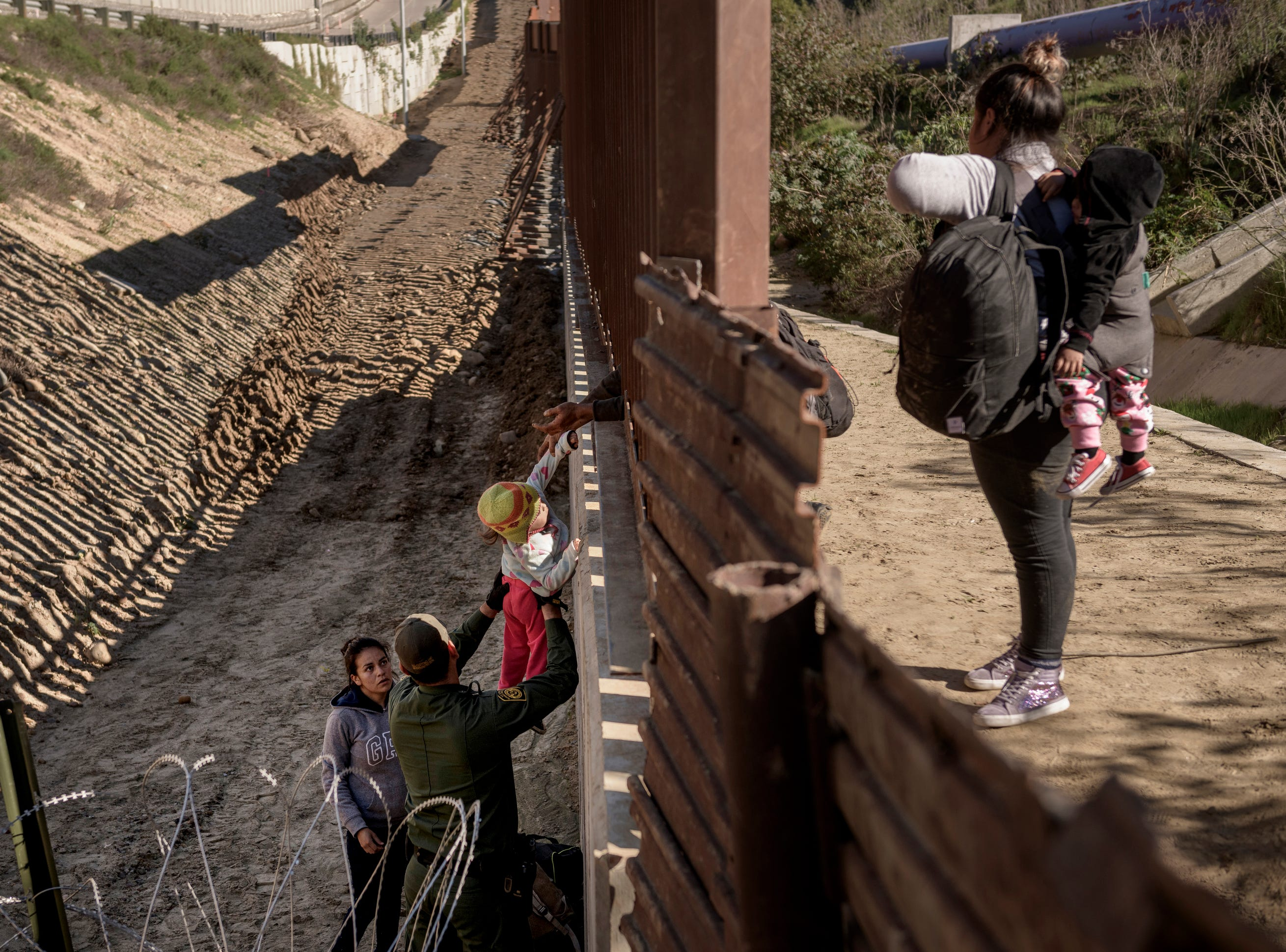A Border Patrol officer holds a baby as he helps a migrant to go down after they jump the border fence to get into the U.S. side to San Diego, Calif., from Tijuana, Mexico, Saturday, Dec. 29, 2018.