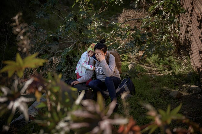 A migrant and her baby pause before jumping the border fence to get into the U.S. side to San Diego, Calif., from Tijuana, Mexico, Saturday, Dec. 29, 2018.