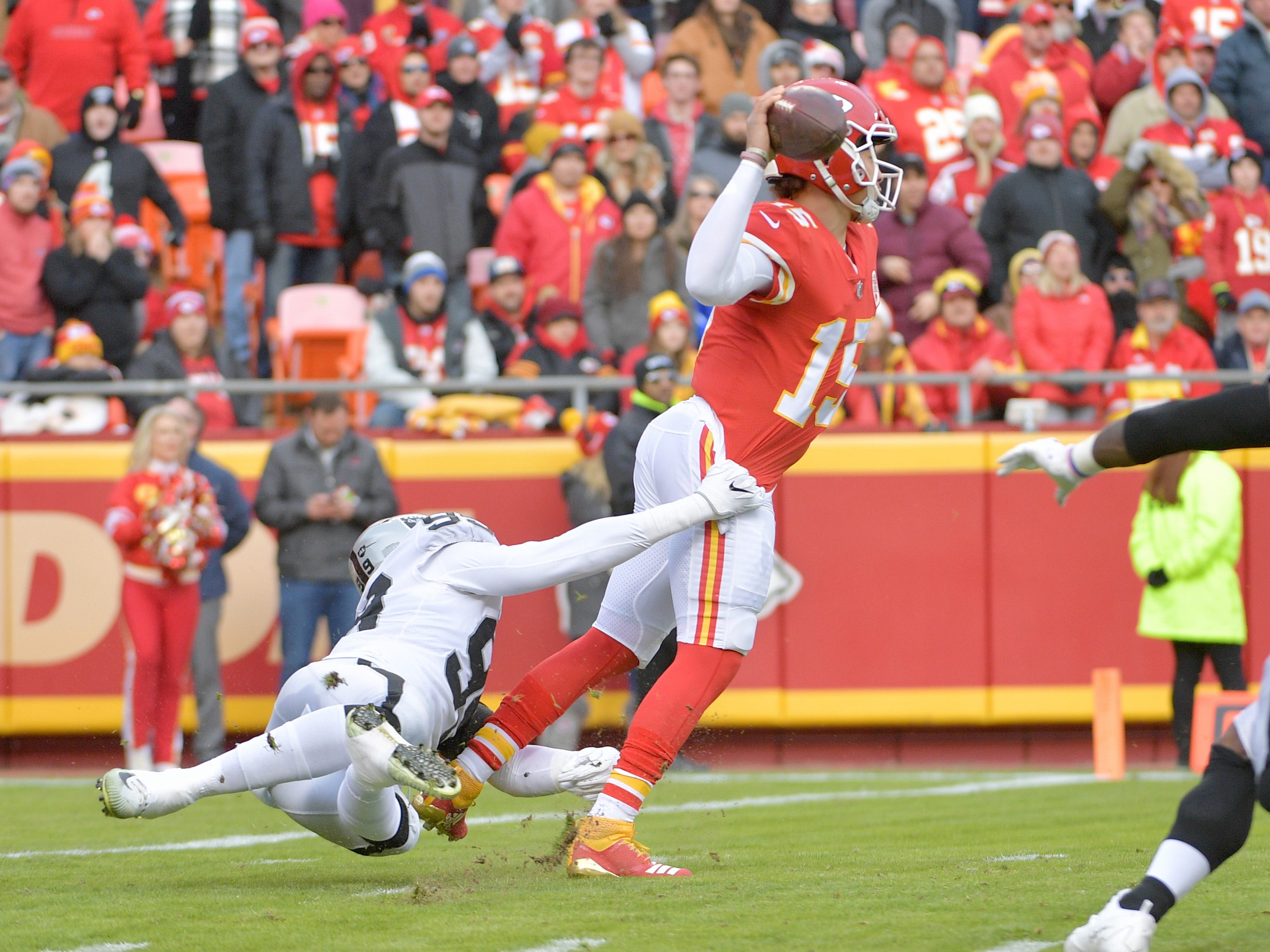 Kansas City Chiefs quarterback Patrick Mahomes (15) throws a pass despite the harassment from Oakland Raiders defensive end Arden Key (99) during the first half at Arrowhead Stadium.