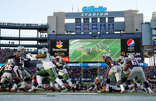New England Patriots quarterback Tom Brady (12) gets off a pass under pressure from New York Jets defensive tackle Mike Pennel (98) during the second half at Gillette Stadium.