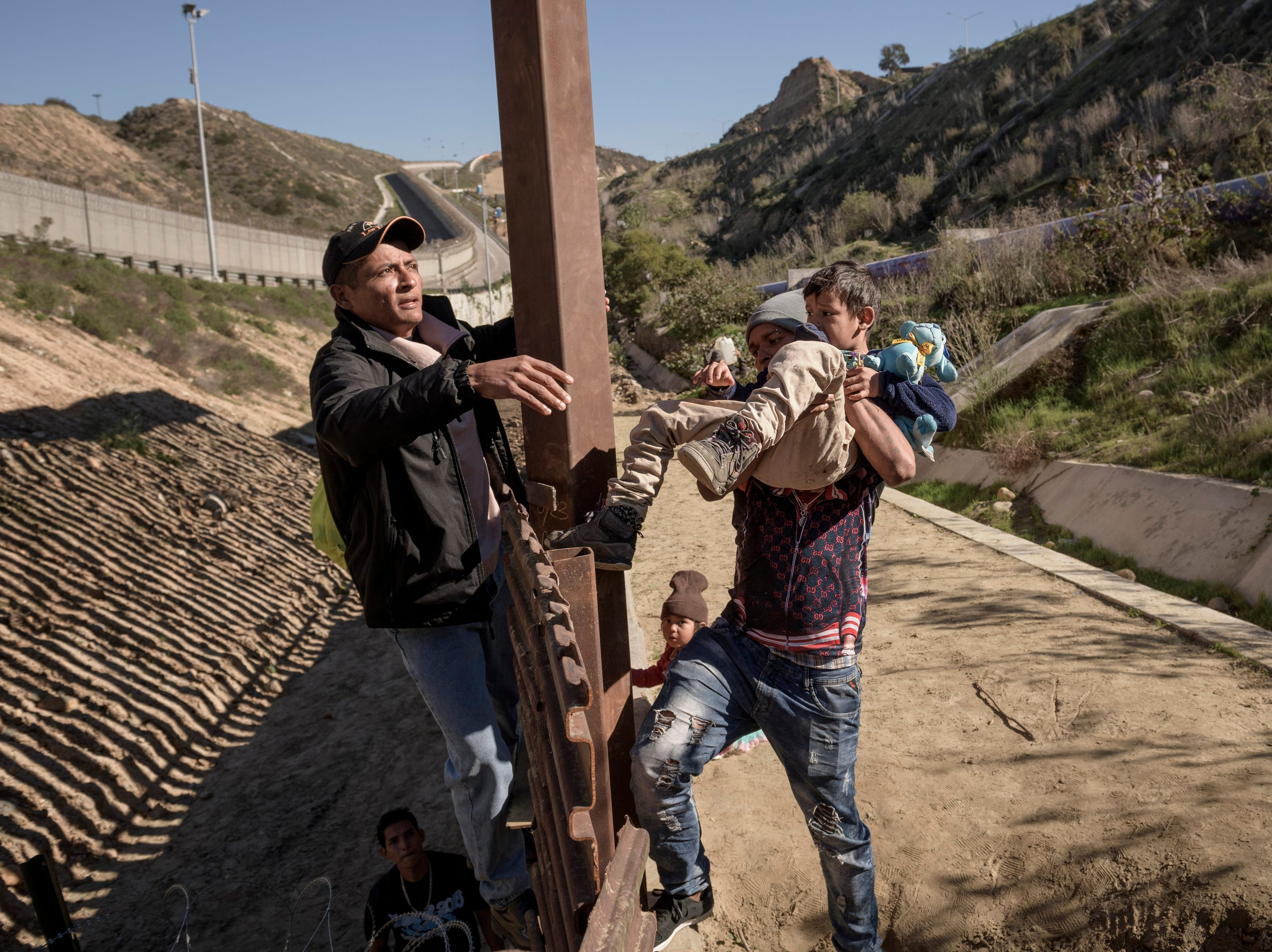 A man holds a Mexican migrant child as he jumps the border fence to get into the U.S. side to San Diego, Calif., from Tijuana, Mexico, Saturday, Dec. 29, 2018.