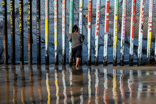 A girl from Salvador, part of the Central American migrants hoping to reach the United States, looks through the US-Mexico border fence in Playas de Tijuana, Baja California State, Mexico, on Dec. 29, 2018.