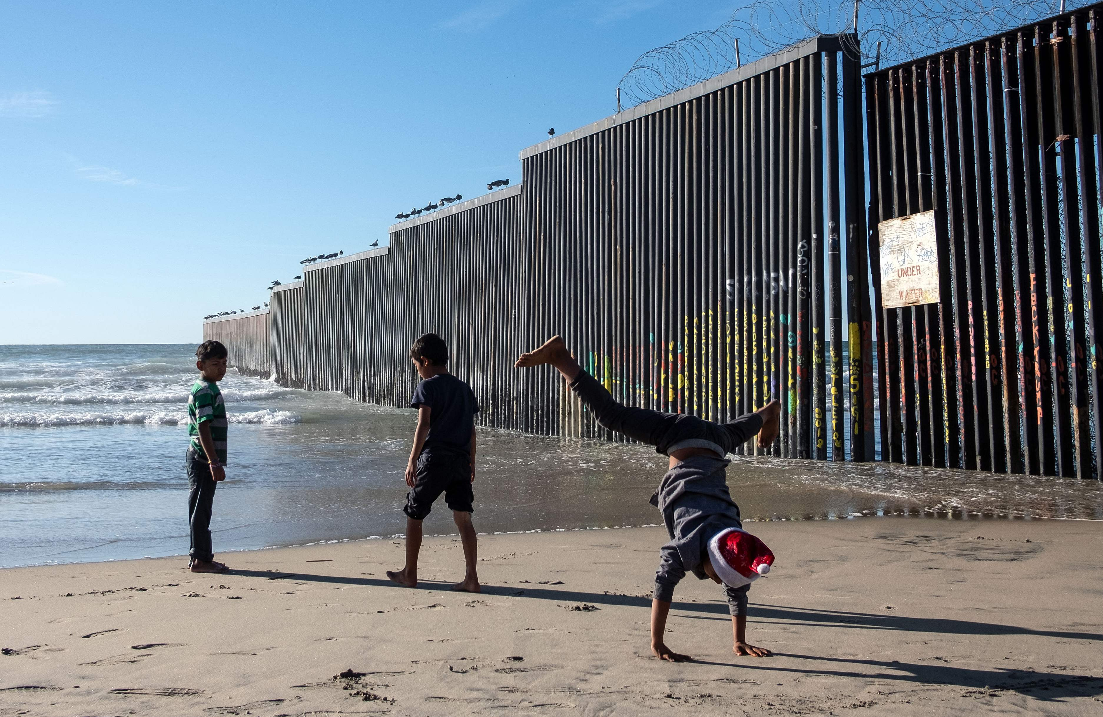 Children traveling with the Central American migrants that hope to reach the United States, play at the beach next to the U.S.-Mexico border fence in Playas de Tijuana, Baja California State, Mexico, on Dec. 29, 2018.