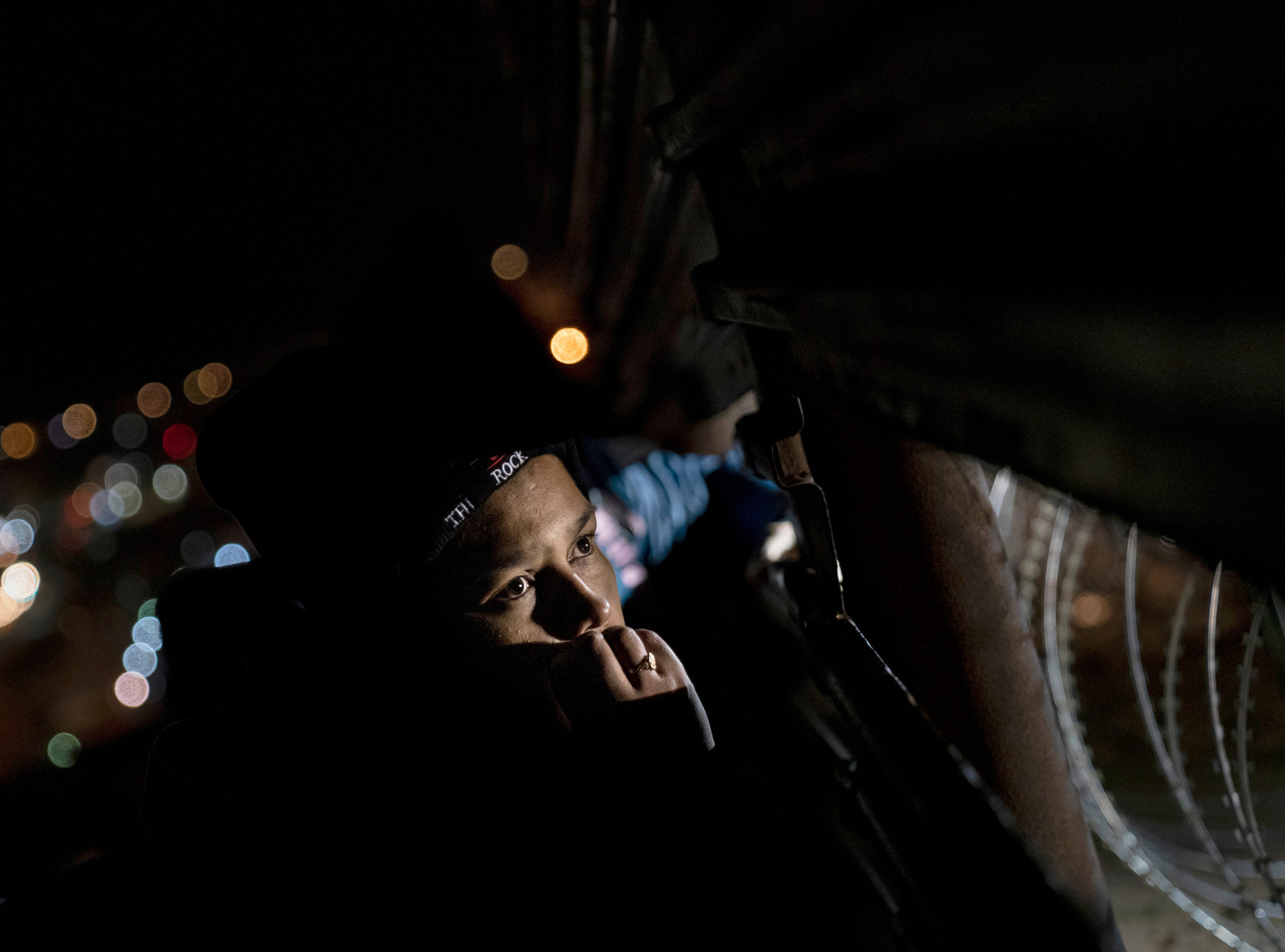 Migrants look trough a hole on the fence as they are looking for a place to jump the border fence to get into the U.S. side to San Diego, Calif., from Tijuana, Mexico, Saturday, Dec. 29, 2018. Discouraged by the long wait to apply for asylum through official ports of entry, many migrants from recent caravans are choosing to cross the U.S. border wall and hand themselves in to border patrol agents.