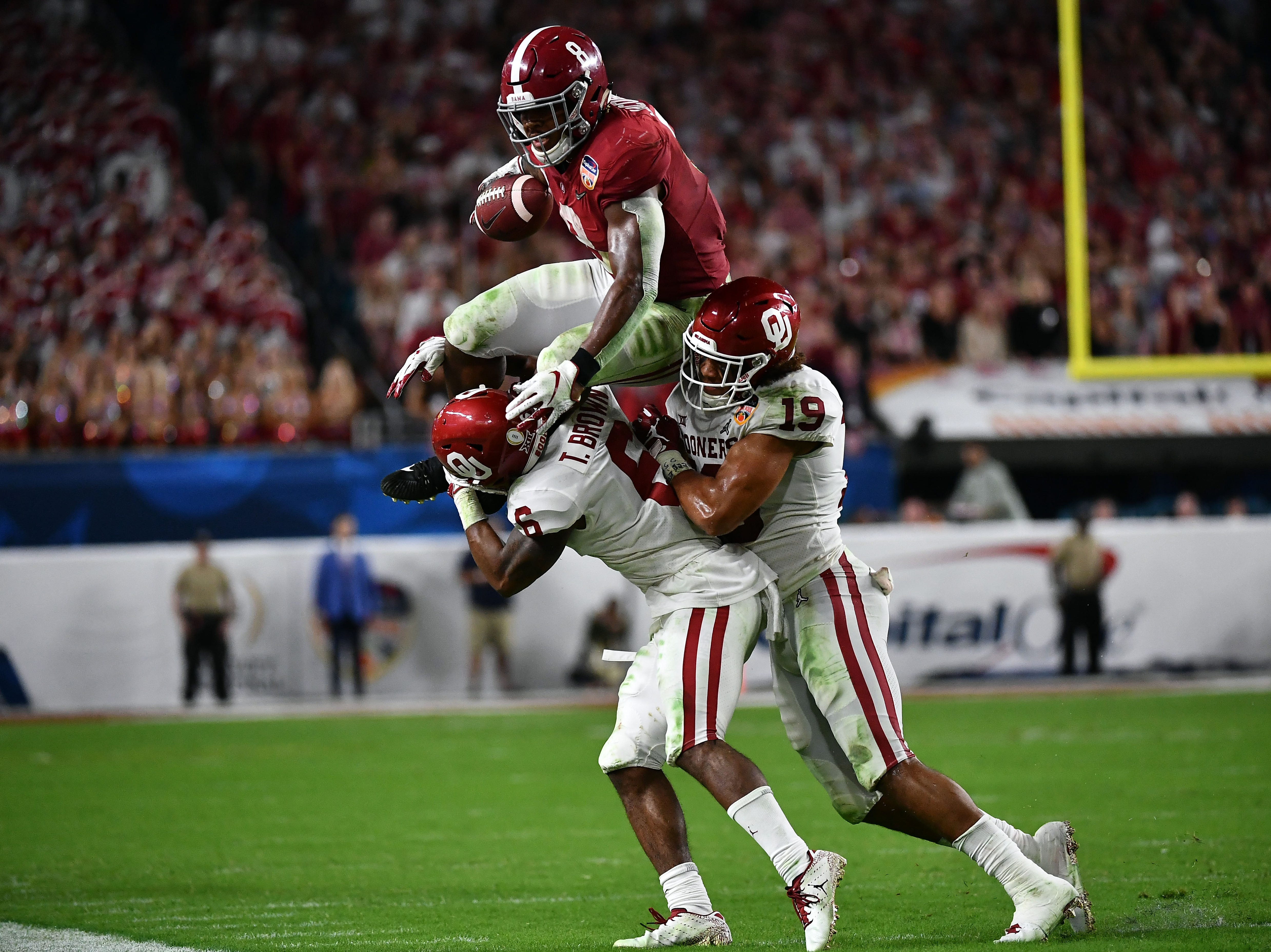Dec. 29: Alabama Crimson Tide running back Josh Jacobs (8) attempts to jump over Oklahoma Sooners cornerback Tre Brown (6) and linebacker Caleb Kelly (19) during the Orange Bowl.