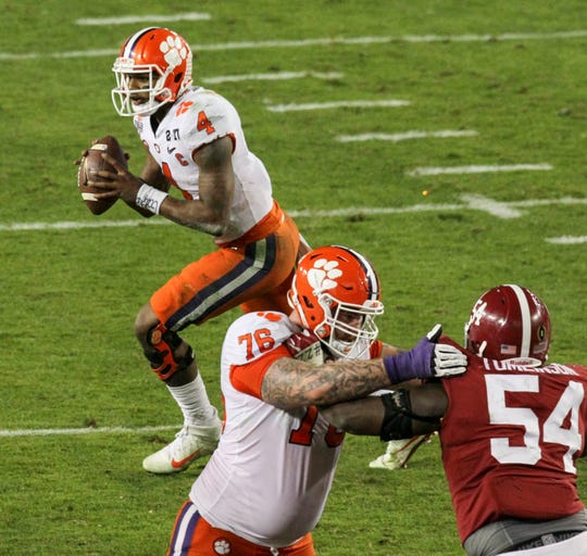 Clemson quarterback Deshaun Watson (4) rolls out to throw to receiver Hunter Renfrow (13) for the winning touchdown during the fourth quarter of the National Championship game on Monday at Raymond James Stadium in Tampa, Florida.