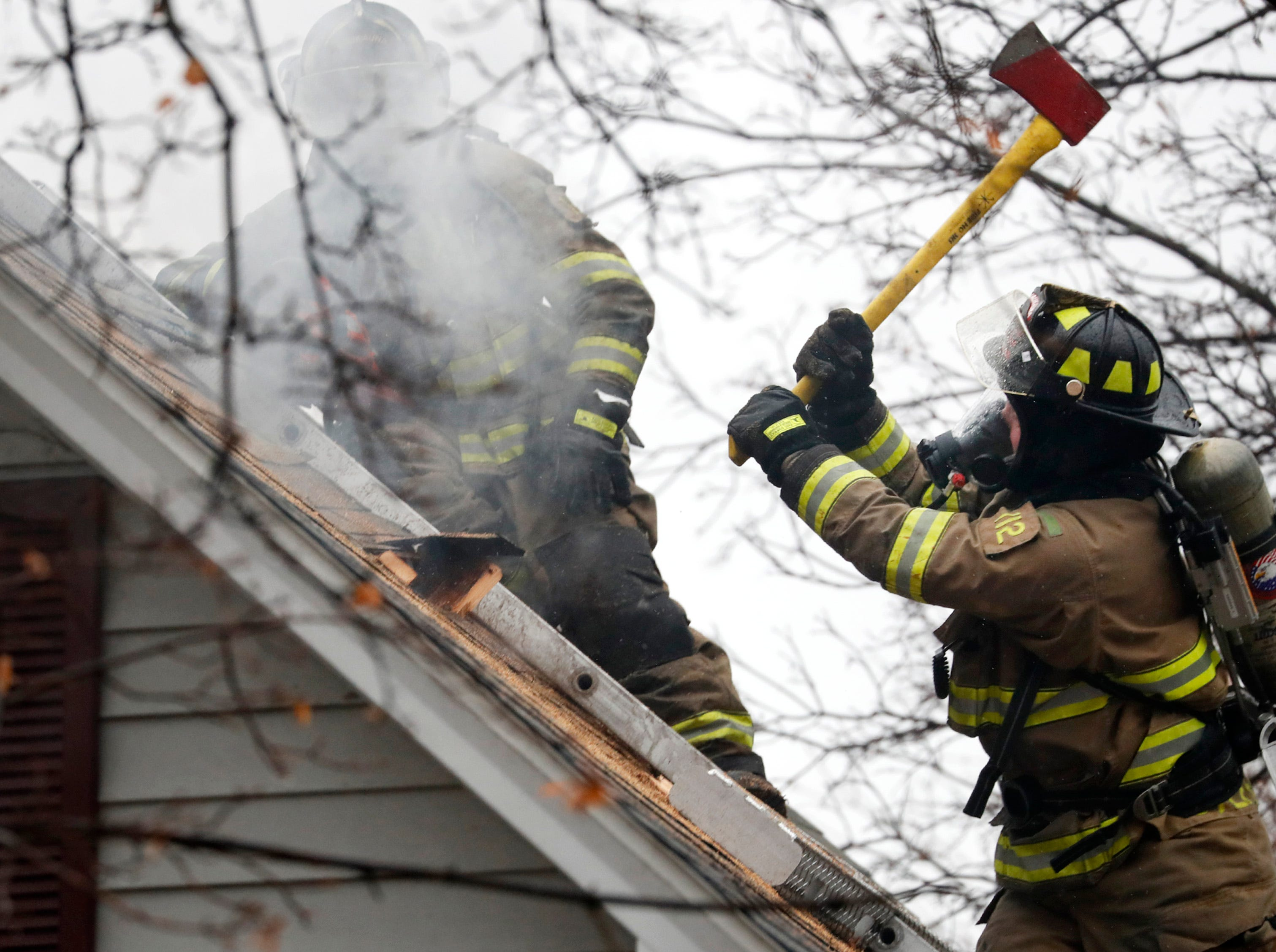 Firefighters work to make a hole in the roof of a building while putting out a structure fire on West 10th Street Thursday, Dec. 27, 2018, Kaukauna, Wis.