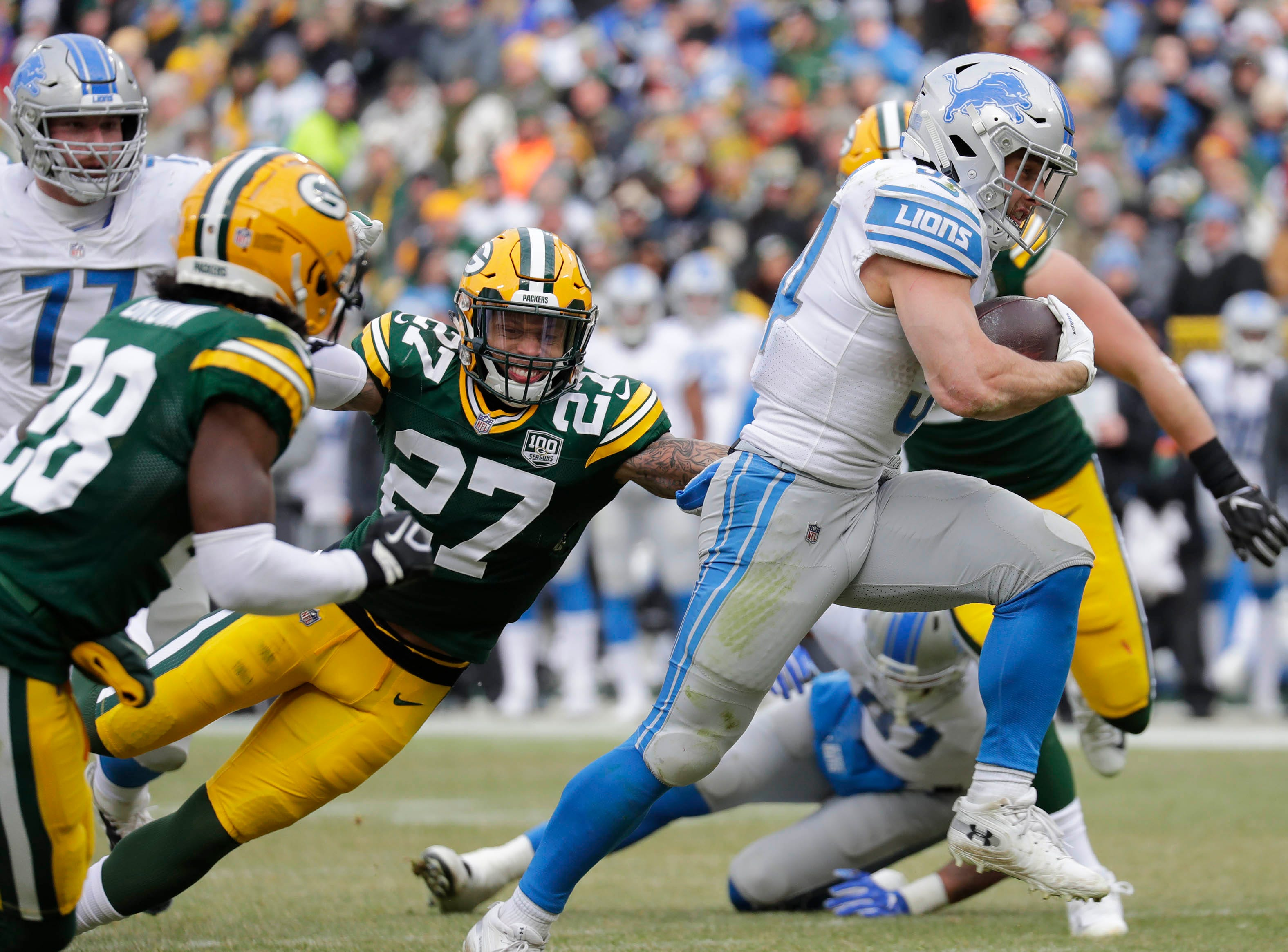 Detroit Lions running back Zach Zenner (34) breaks away for a touchdown run against defensive back Tony Brown (28) and defensive back Josh Jones (27) late in the second quarter Sunday, December 30, 2018, at Lambeau Field in Green Bay, Wis. 