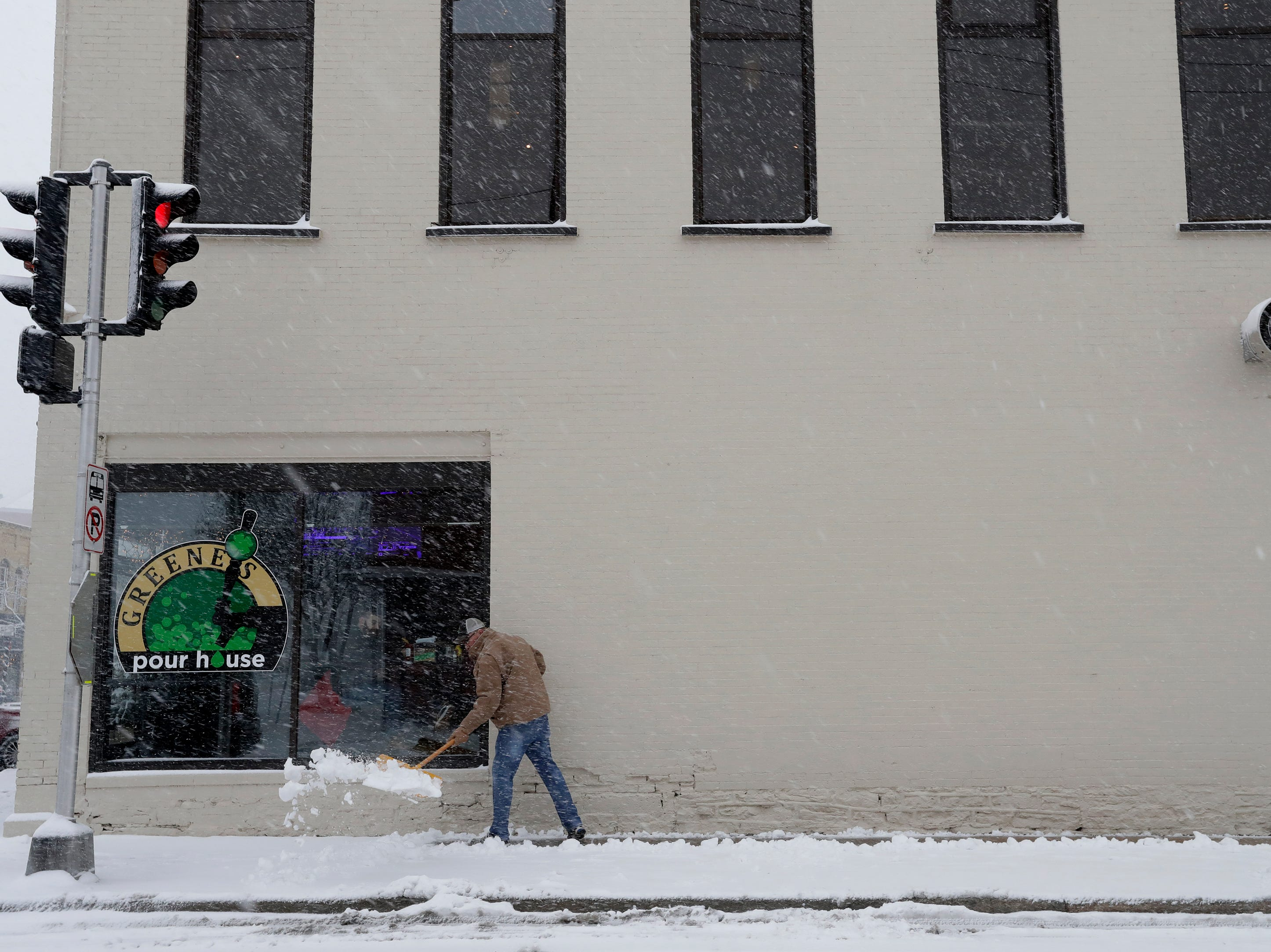 Jay Van Handel, manager of Greene's Pour House, clears snow from the sidewalks during a snow storm Monday, December 31, 2018, in downtown Neenah, Wis. Dan Powers/USA TODAY NETWORK-Wisconsin