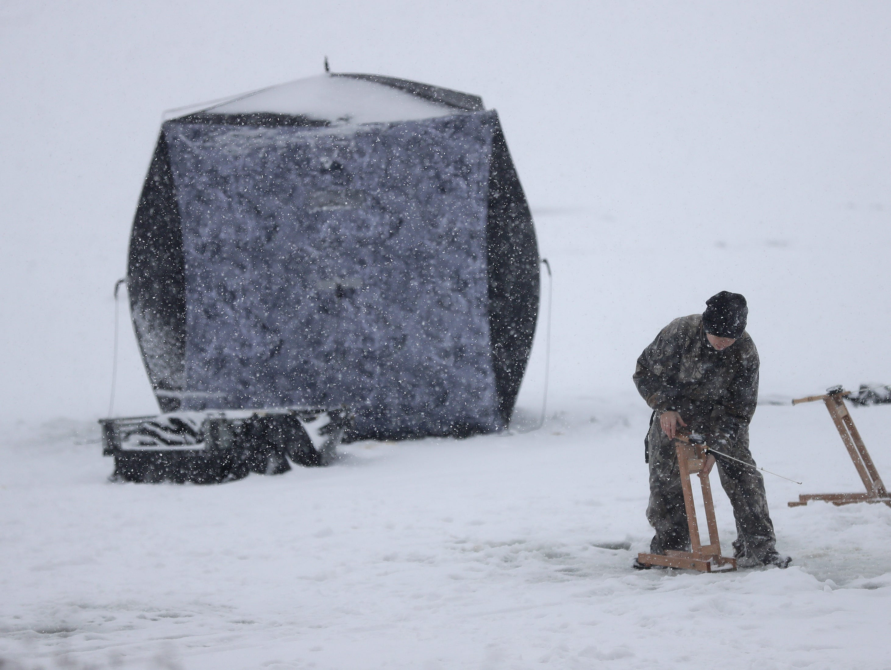 Isiah Schuh, 13, of Little Chute sets up a tip down while ice fishing with his father during a snow storm on Little Lake Butte des Morts Monday, December 31, 2018, in Fox Crossings, Wis. Dan Powers/USA TODAY NETWORK-Wisconsin