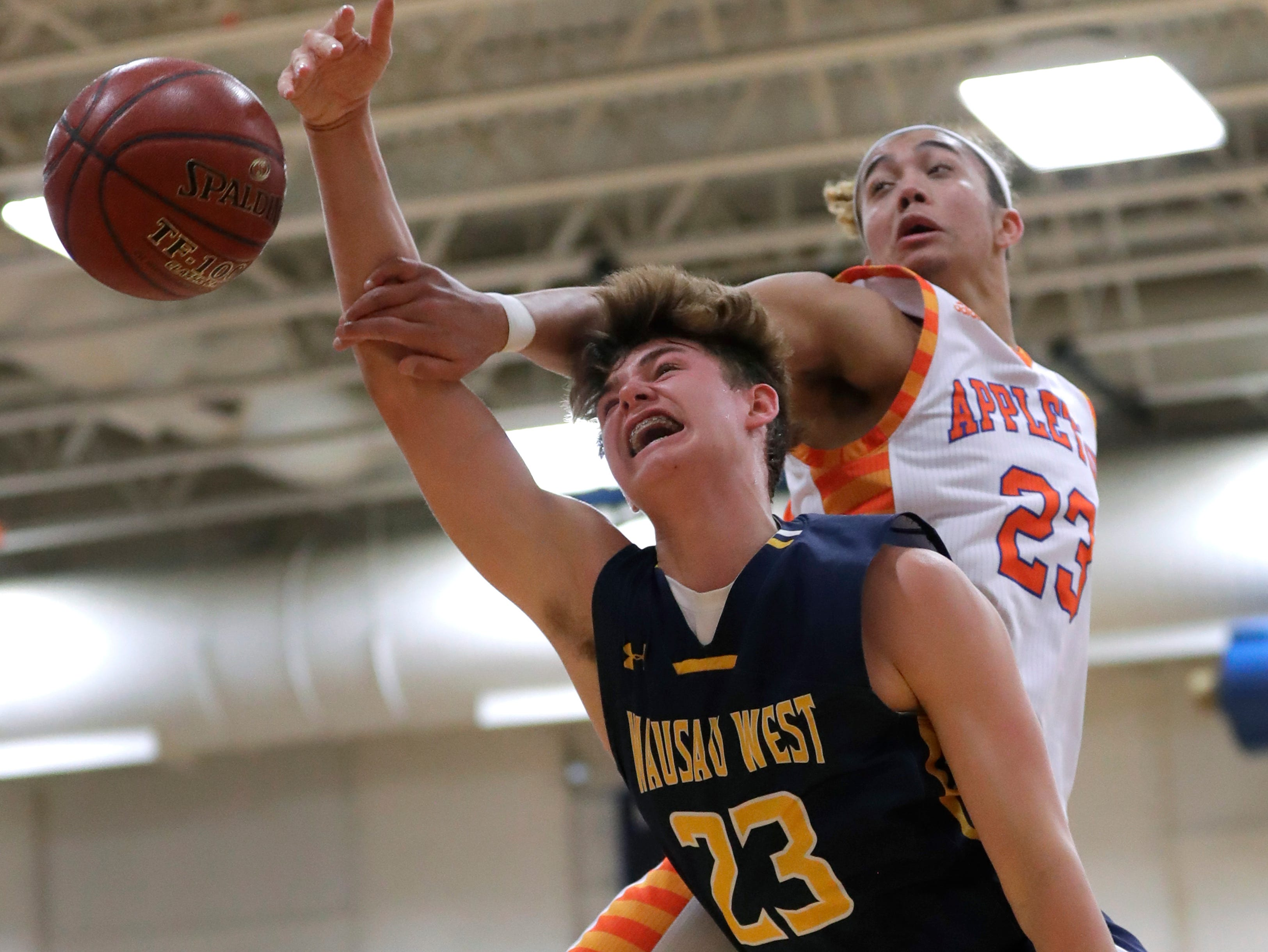 Appleton West  High School's Bubba Thompson (23) fouls Wausau West High School's Logan White (23) as he puts up a shot during their boys basketball game Friday, December 28, 2018, in Appleton, Wis. 