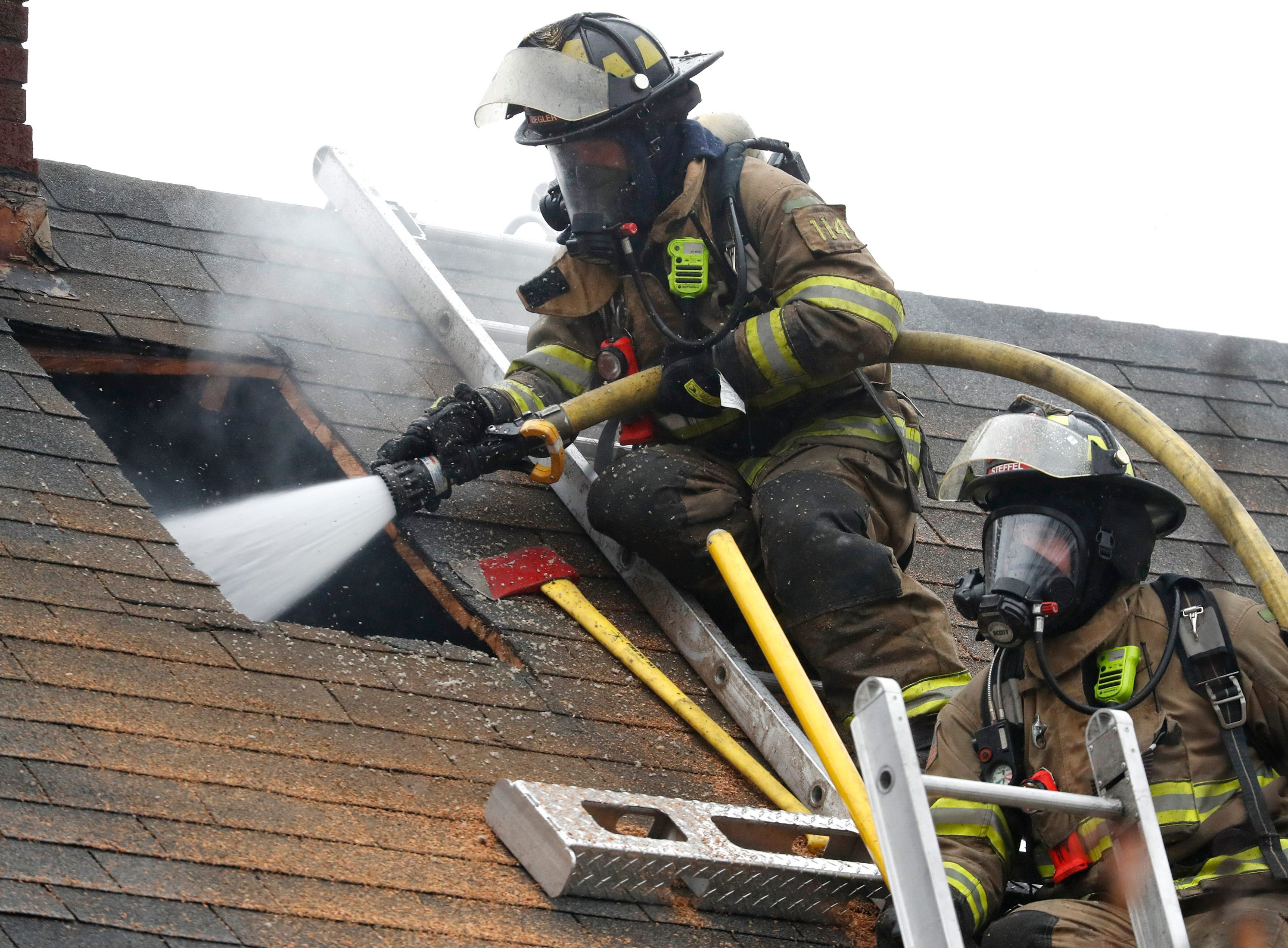 Kaukuana Firefighters spray water through a hole they cut in the roof of a building on West 10th Street Thursday, Dec. 27, 2018, Kaukauna, Wis.