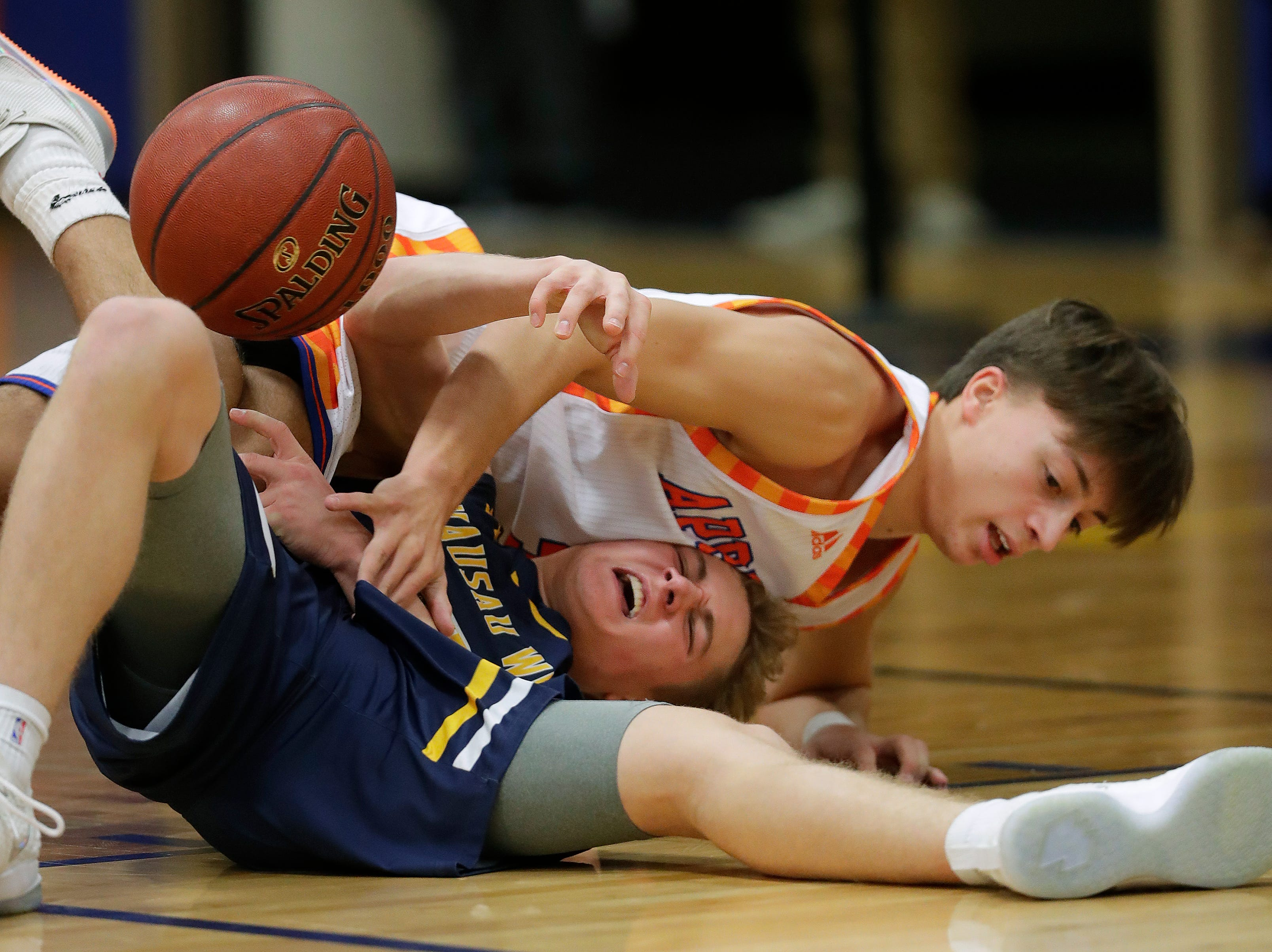 Appleton West  High School's Eli Vogel, top, battles for a loose ball against Wausau West High School's Mitchell Zahurones during their boys basketball game Friday, December 28, 2018, in Appleton, Wis. 