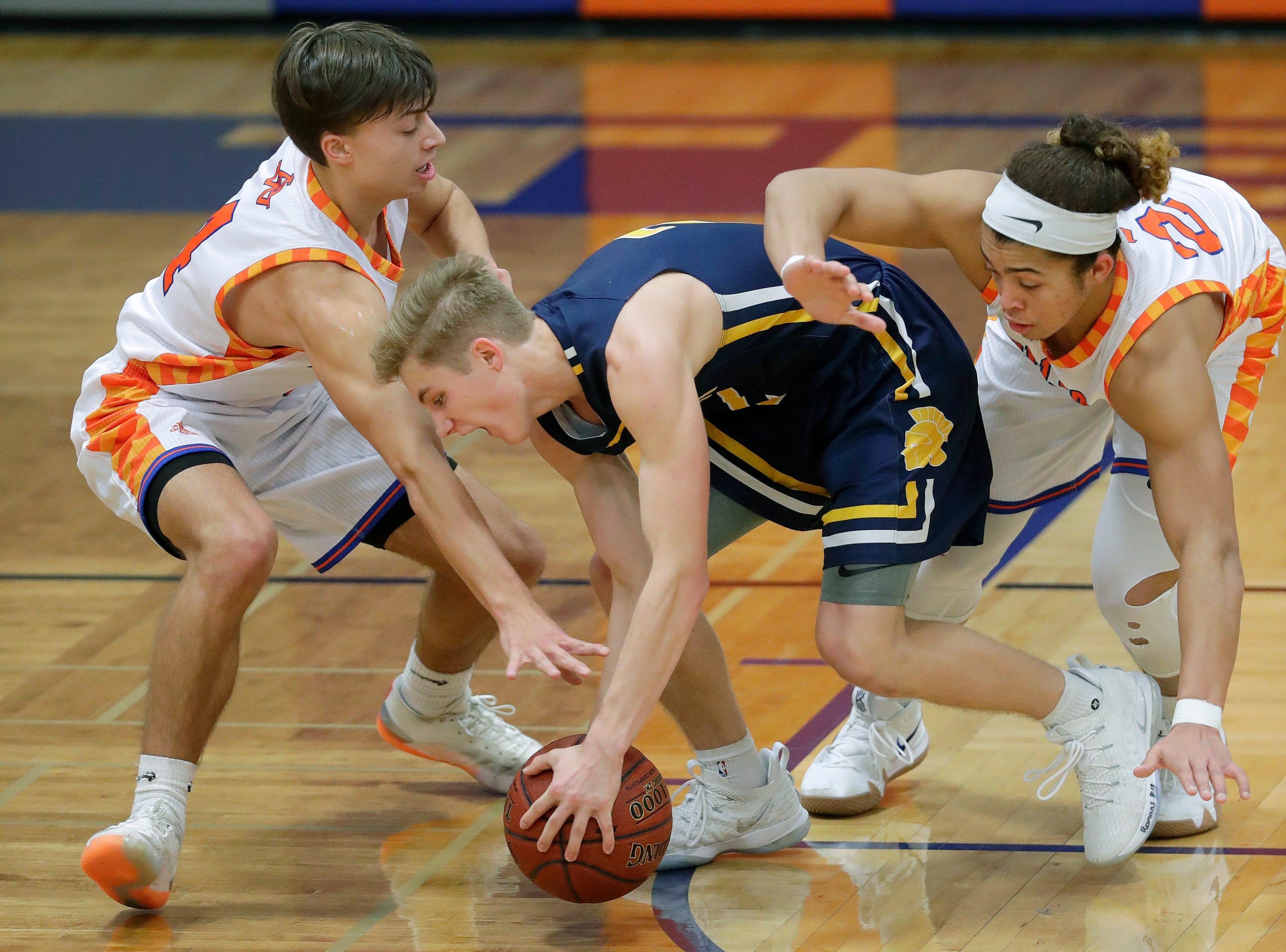 Appleton West  High School's Eli Vogel , left, and Bubba Thompson, right, defend against Wausau West High School's Mitchell Zahurones (2) during their boys basketball game Friday, December 28, 2018, in Appleton, Wis. 