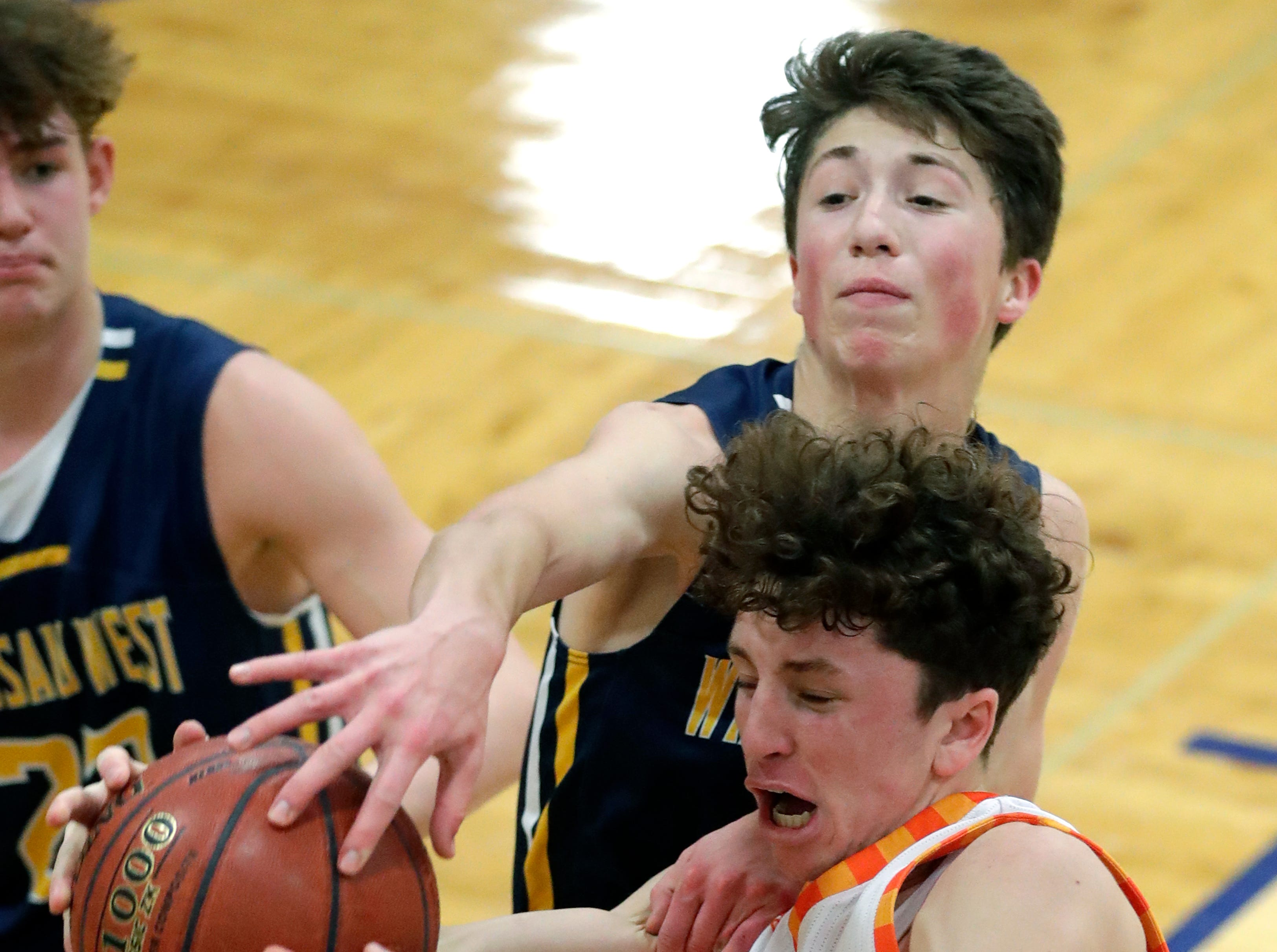 Appleton West  High School's Will Mahoney (21) is fouled as he puts up a shot against Wausau West High School's Tim Deloye (11) during their boys basketball game Friday, December 28, 2018, in Appleton, Wis. 
