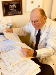 Dr. Barry Grabelle reviews papers in his Eatontown office.